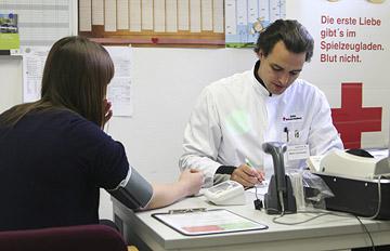 Foto: Blutdruckmessen und Ausfüllen eines Fragebogens durch den Arzt