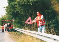 Foto: Eine Person stellt ein Warndreieck auf.