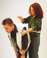 Foto: Eine Frau schlägt einem Mann zwischen die Schulterblätter.