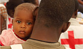 Baby im Arm von Rotkreuzhelfer