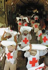 Foto: Viele Helfer entladen Hilfsgüter aus einem Flugzeug
