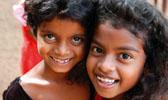 Foto: Zwei lachende Mädchen schmiegen sich aneinander.