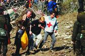 Foto: Ein Rotkreuzhelfer stützt Flüchtlinge, um durch die Grenzzone zu kommen - vorbei an bewaffneten Männern.